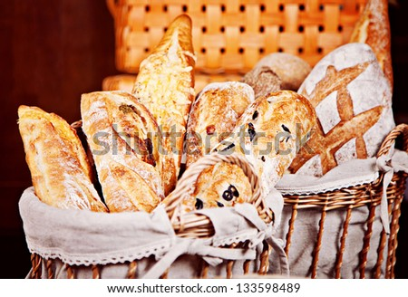 Fresh mix of baguettes in baskets - stock photo