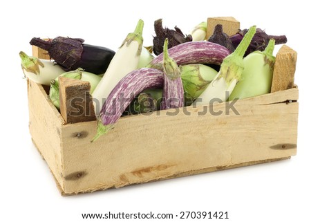 fresh mixed aubergines (Cucurbita pepo) in a wooden crate on a white background - stock photo