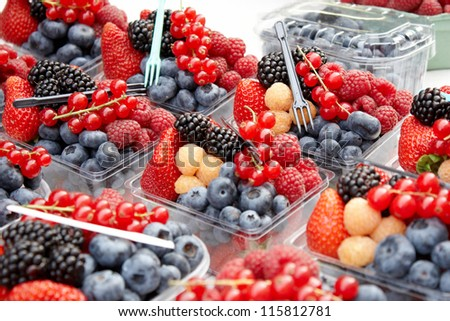 Fresh mixed berries for sale in an outdoor market - stock photo
