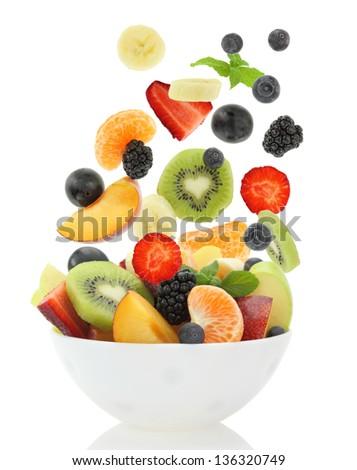 Fresh mixed fruit salad falling into a bowl of salad - stock photo