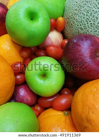 fresh mixed fruits,green apples,red apples,oranges melon and tomotoes