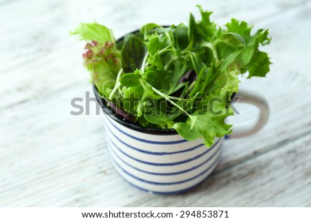 Fresh mixed green salad in cup on wooden table close up