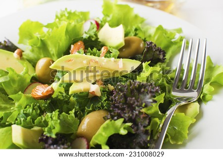 Fresh mixed green salad with avocado close up - stock photo