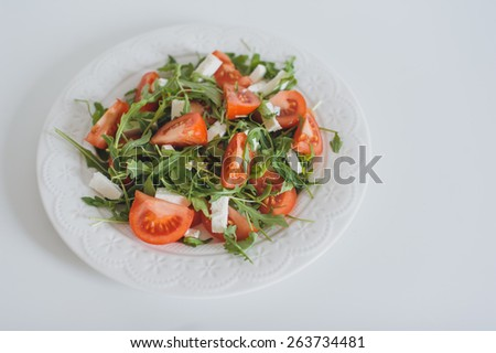 Fresh mixed mediterranean salad with feta cheese, tomato and arugula served in a plate on white background - stock photo