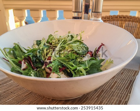 Fresh mixed salad in a white bowl on a restaurant table  Fresh mediterranean salad in a white bowl on table with balsamico and olive oil in background. Healthy food for vegetarians and low carb diet - stock photo