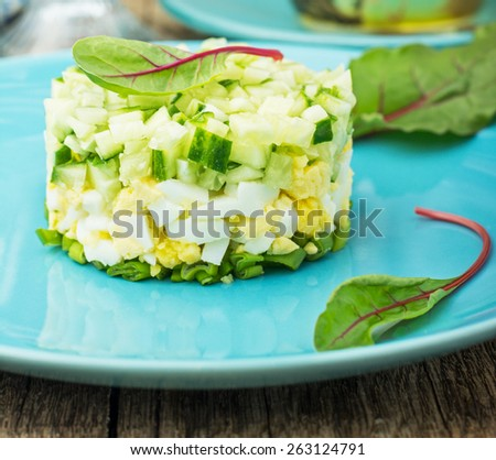 Fresh mixed salad with eggs, cucumber, green onions, chard on a bright blue plate on a wooden background in the form of towers.... - stock photo