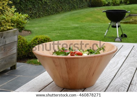 Fresh mixed summer salad in wooden bowl. Barbecue unit on green grass in the background.