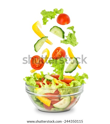 Fresh mixed vegetables falling into a bowl of salad. Isolated on white. - stock photo