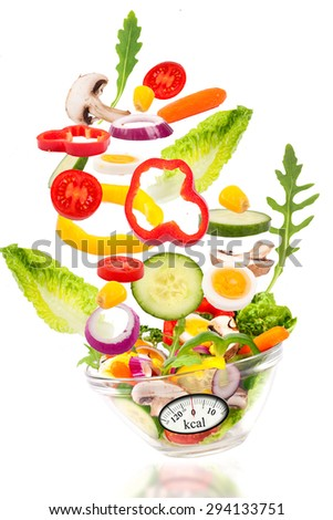 Fresh mixed vegetables falling into a bowl of salad with analogous weight scale. Diet concept - stock photo