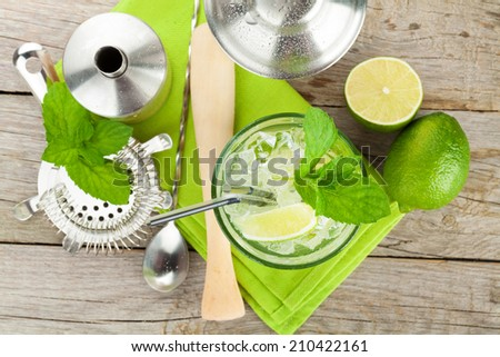 Fresh mojito cocktail and bar utensils on wooden table - stock photo
