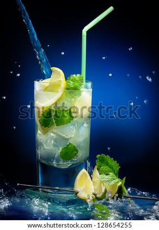Fresh mojito cocktail  on wet dark blue background - stock photo