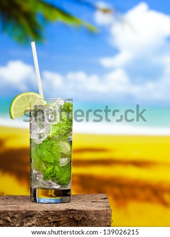 Fresh mojito cocktail on wooden table on sky and sand background - stock photo