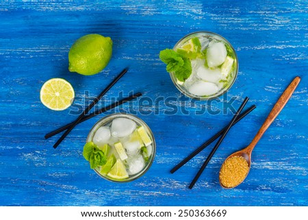 Fresh mojito drink on the blue wooden table - stock photo