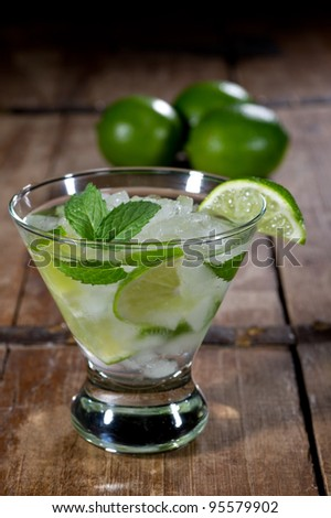 Fresh mojito in a lowball glass on a rustic table garnished with limes and mint leaves. - stock photo