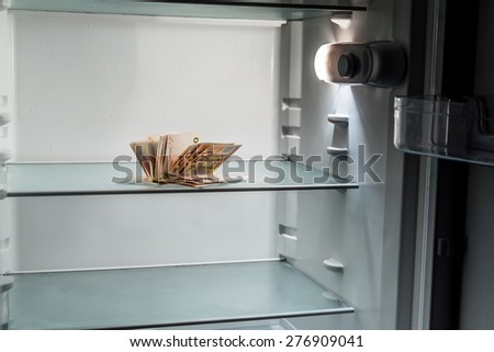 Fresh money in the refrigerator: a handful of 50 euros banknotes illuminated by cold light of an empty refrigerator