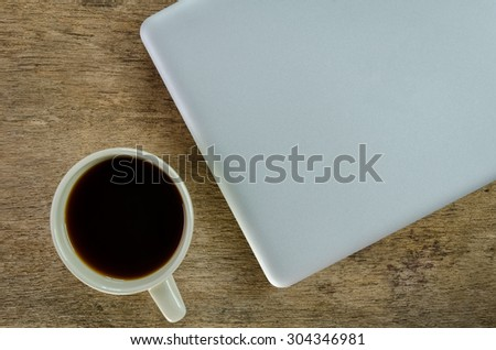 fresh morning coffee with laptop on old wooden table background