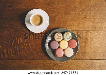 Fresh morning espresso coffee and some french macarons dessert on the wooden table background - stock photo
