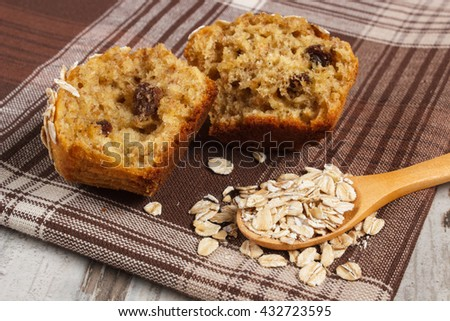 Fresh muffin with oatmeal baked with wholemeal flour on checkered tablecloth, concept of delicious, healthy dessert or snack