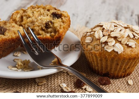 Fresh muffins with oatmeal baked with wholemeal flour on white plate and fork, concept of delicious, healthy dessert or snack - stock photo