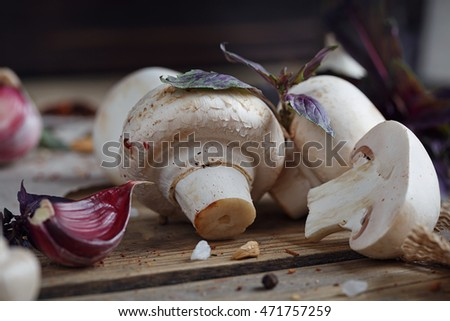 Fresh mushrooms and garlic on wooden background