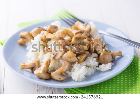 Fresh mushrooms and rice on platelon white table. Selective focus. Rustic style. - stock photo