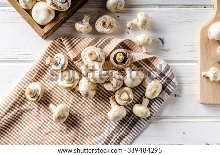 Fresh mushrooms cleaning and cutting, white wood table - stock photo