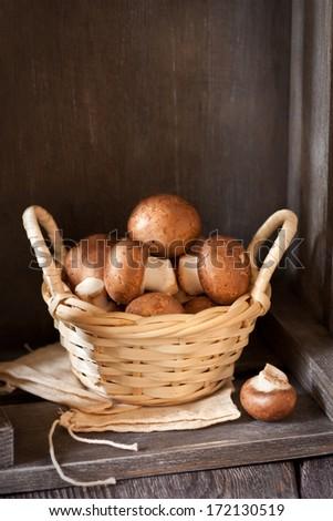 Fresh mushrooms in a small wicker basket. - stock photo