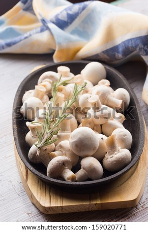 Fresh mushrooms in bowl on white table. Selective focus. Rustic style. - stock photo