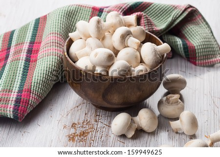 Fresh mushrooms in wooden bowl on white table. Selective focus. Rustic style. - stock photo