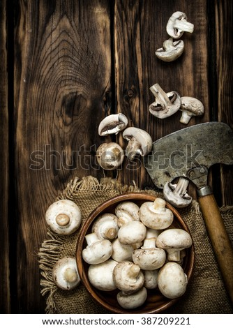 Fresh mushrooms with an old hatchet. On wooden background.