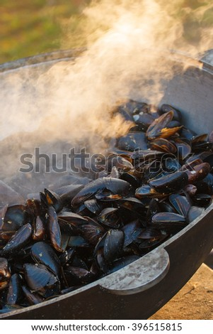 Fresh mussels cooked in a cauldron on the nature - stock photo