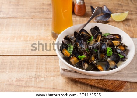 Fresh mussels on a plate on a wooden background, selective focus - stock photo