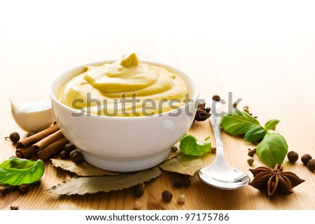 Fresh mustard in a bowl with spices and a spoon - stock photo