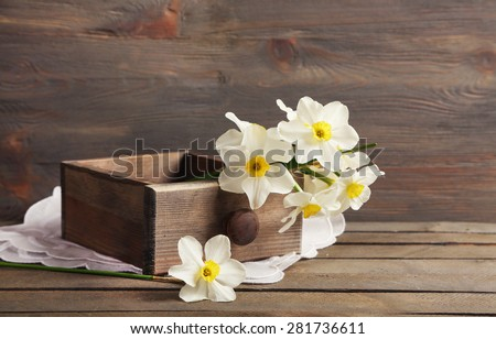 Fresh narcissus in chest on wooden background - stock photo