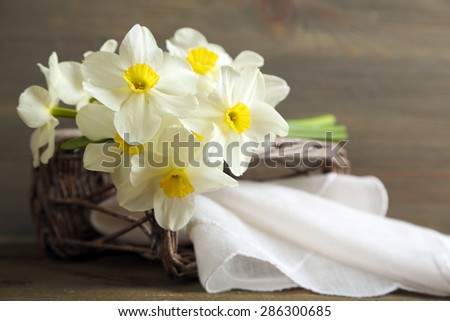 Fresh narcissus with wicker basket on wooden background - stock photo