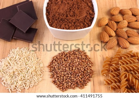 Fresh, natural ingredients and products containing magnesium and dietary fiber, healthy food and nutrition, wholemeal pasta, buckwheat, brown rice, almonds, cocoa, chocolate - stock photo