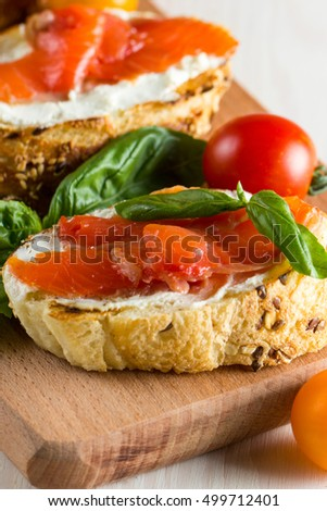 Fresh natural Italian tomato, salmon and cheese bruschetta. Tapas, antipasti with chopped vegetables, herbs and oil on grilled ciabatta and baguette bread.