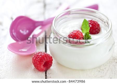 fresh natural yogurt with raspberries in a glass - stock photo