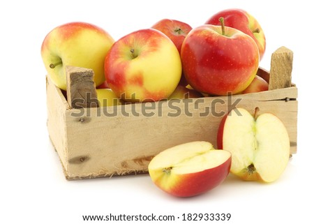 "fresh new Dutch apple variety called ""Kanzi""  and a cut one in a wooden crate on a white background"