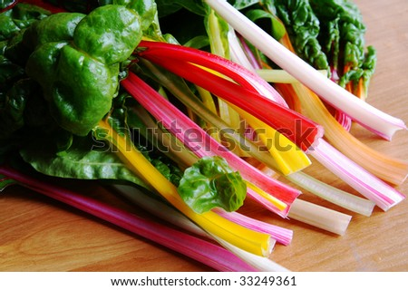 Fresh new mangold crops (also called as chard, perpetual spinash, mangel, wurzel, crab beet, silverbeet) of different colors on a kitchen table with water drops - stock photo
