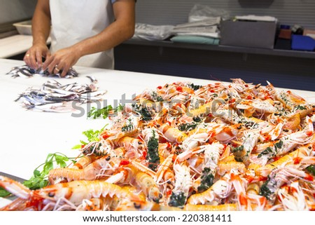 Fresh Norway lobsters and hands preparing fish at market. - stock photo