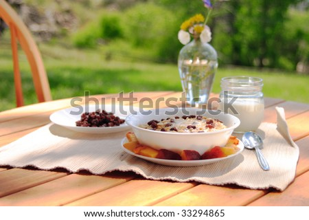 Fresh oatmeal topped with raisins, melted butter, and brown sugar with peaches and milk just waiting to be added. - stock photo