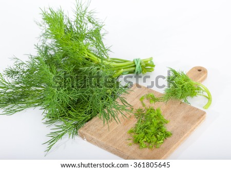 Fresh of dill. Bunch of dill and wooden board with chopped dill.