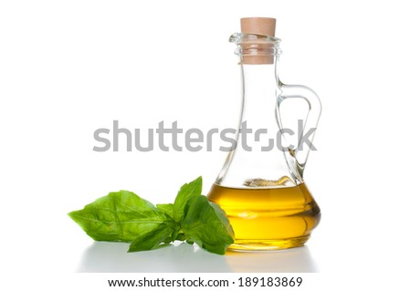 Fresh olive oil in a glass bottle and a sprig of basil on a white background isolated