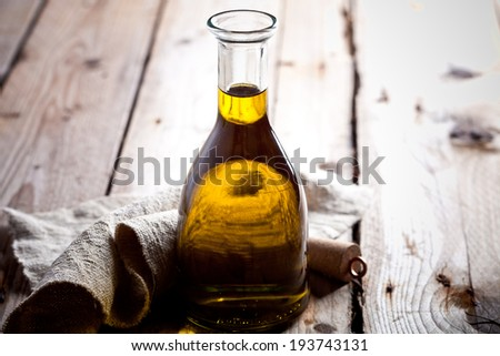 fresh olive oil in bottle on rustic wooden board - stock photo