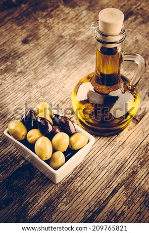 Fresh olives and olive oil on rustic wooden background - stock photo