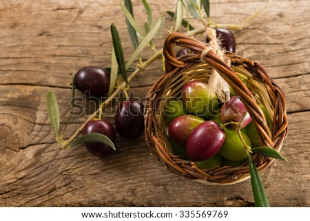 fresh olives in a basket, placed on a rustic wooden table. Olives from Sicily, Italy - stock photo