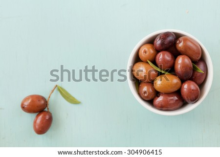 Fresh olives in white bowl on rustic wooden table - stock photo