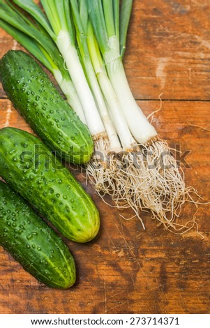 Fresh onion and cucumbers on old rustic wooden table - stock photo