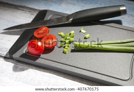 Fresh onion leafs and tomatoes on chopping board - stock photo
